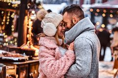 Couple in love, a stylish couple wearing warm clothes cuddling together and looking each other at the winter fair at a. An attractive couple in love, a stylish stock images