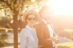 A couple in love at sunset in hats stand with their backs in th. E frame. American dream. A retro couple in his country house, his estate. Lovestory, family day stock photography