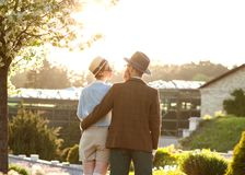 A couple in love at sunset in hats stand with their backs in th. E frame. American dream. A retro couple in his country house, his estate. Lovestory, family day royalty free stock photos