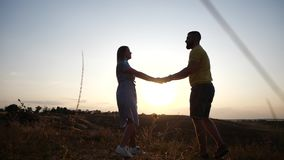 A love story of a young charming couple holding hands in rural landscape at sunset. Silhouette of bearded young man and. A couple in love in the sunset light stock video footage