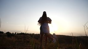 A love story of a young charming couple in rural landscape at sunset. Silhouette of bearded young man holding and. A couple in love in the sunset light. Young stock video footage