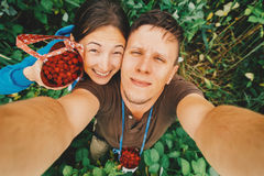 Couple in love taking self-portrait in summer raspberry garden. Happy young couple in love taking self-portrait in summer garden with raspberries Royalty Free Stock Image