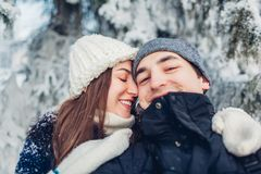 Couple in love taking selfie and hugging in winter forest. Young happy people having fun. Valentine`s day royalty free stock image