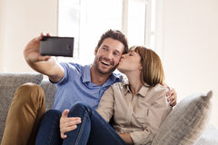 Couple in love taking a selfie with a mobile phone.She kisses him Royalty Free Stock Photo