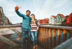Couple in love taking selfie by smartphone traveling together in Norway Stock Images