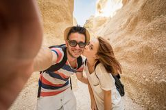 Love couple taking a selfie hiking on vacation. Couple in love taking a selfie smiling at the camera on vacation during an adventure hiking GrandCanyon stock image
