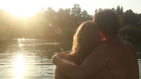 Couple in love taking selfies while sitting by the river at sunset stock video