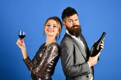 Couple in love tasting wine with smiling and tricky faces. Winetasting, celebrating concept. Man with beard, women in dress on blue background. Lady and Stock Images