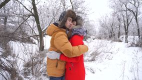 Couple in love. Teenagers. Winter. Couple in love. Teenagers on a date in the winter outdoors. Girlfriend and boyfriend are kissing and talking. Strong embrace stock video footage