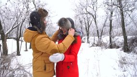 Couple in love. Teenagers. Winter. Couple in love. Teenagers on a date in the winter outdoors. The guy puts a hat on his girlfriend head and kisses her. Strong stock video
