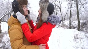 Couple in love. Teenagers. Winter. Couple in love. Teenagers on a date in the winter outdoors. Girlfriend straightens his hat to her boyfriend and kisses him stock video