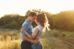 Couple in love. Tenderness and embrace. The guy and the girl look into each other`s eyes. Sunset sun over the forest Royalty Free Stock Images