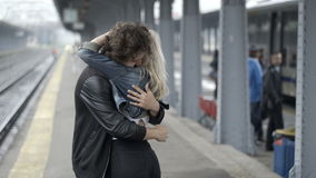 Couple in love tickling and kissing in train station having fun before departure waiting the train. Teenage couple in love tickling and kissing in train station stock footage