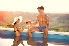 Couple in love toasting with cocktail in pool Stock Images