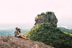 A couple in love on a rock admires the beautiful views royalty free stock image