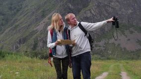 Couple in love travels in the mountains with a map and binoculars. Friends travelers are looking for directions on the. Map. man and woman tourists in the stock footage