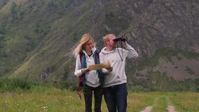 Couple in love travels in the mountains with a map and binoculars. friends travelers are looking for directions on the. Map. man and woman tourists in the stock video