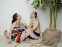 Couple in love under the palm. Young couple under a palm tree in the Studio Stock Images