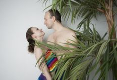 Couple in love under the palm. Young couple under a palm tree in the Studio Stock Photos