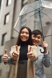 Couple in love under umbrella in background of mall. Royalty Free Stock Photography