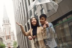 Couple in love under umbrella in background of mall. Stock Photos