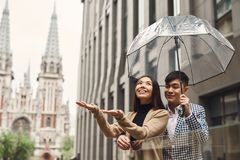Couple in love under umbrella in background of mall. Stock Photography