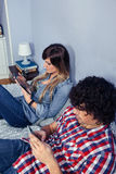 Couple in love using electronic devices on bed Royalty Free Stock Image