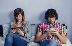 Couple in love using electronic devices on bed Stock Photo