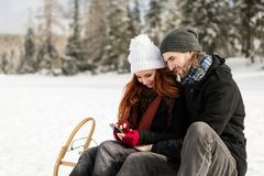 Couple in love using mobile while sitting on sleigh Royalty Free Stock Photos