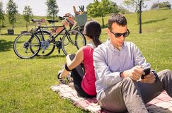 Couple in love using a smartphones on the park Stock Photo