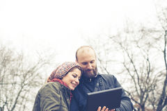 Couple in love using tablet connecting web wireless wifi Royalty Free Stock Images