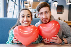 Couple in love in Valentines day. Man and women with balloon in the form of heart in a cafe. Two people communicate, laughing and enjoying the time spending with royalty free stock photo