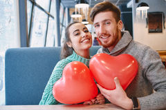 Couple in love in Valentines day. Man and women with balloon in the form of heart in a cafe. Two people communicate, laughing and enjoying the time spending with royalty free stock photography