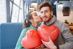 Couple in love in Valentines day. Man and women with balloon in the form of heart in a cafe. women kisses a men on the cheek. Couple in love on a date. Love stock photography