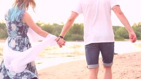 Couple in love on beach. Couple in love walk on beach in spring / summer during sunset near water / river. Date concept stock video