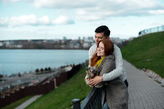 Couple in love walking along the waterfront with her dog. In love beautiful couple walking along the waterfront with her dog Royalty Free Stock Photos