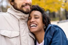Couple in love are walking in the autumn park. Afroamerican girl with a European.  stock image