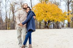 Couple in love are walking in the autumn park. Afroamerican girl with a European.  stock photo
