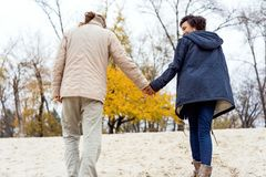 Couple in love are walking in the autumn park. Afroamerican girl with a European.  stock photos