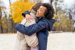 Couple in love are walking in the autumn park. Afroamerican girl with a European.  stock images
