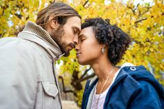 Couple in love are walking in the autumn park. Afroamerican girl with a European.  royalty free stock images
