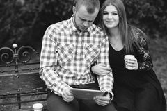 Couple in love. Couple walking through the city, sitting on the bench, photographed and drinking coffee royalty free stock photography