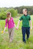 Couple in love walking on meadow Stock Image