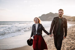 Couple in love walking on sandy beach by the hand. Stock Images