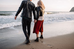 Couple in love walking on sandy beach by the hand. Stock Photos