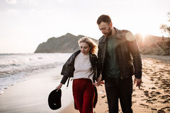 Couple in love walking on sandy beach by the hand. Stock Image