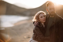 Couple in love walking on sandy beach by the hand. Soft light Royalty Free Stock Photo