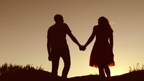 Couple in love walking on silhouette nature sunset slow motion video. Man and woman silhouette of a love walk with a dog stock video footage