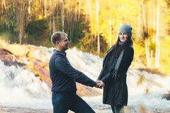 Couple in Love Warm Handclasp. Couple in Love on Autumn River Beach over small Waterfall Stock Photography