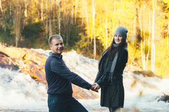 Couple in Love Warm Handclasp. Couple in Love on Autumn River Beach over small Waterfall Royalty Free Stock Photos